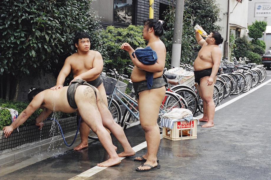 Rishiki (wrestlers) wash themselves with a hose outside Musashigawa-beya.