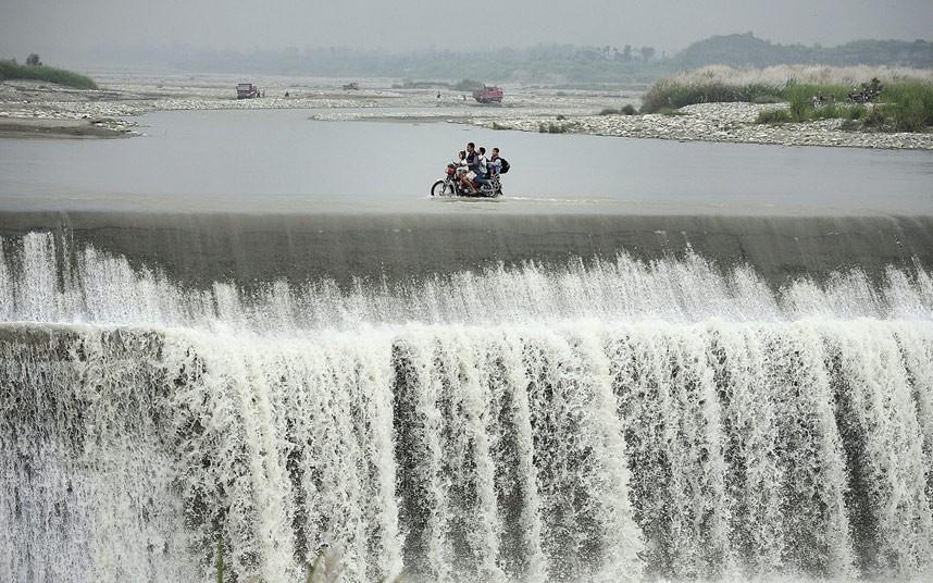 مردی چینی به همراه فرزندانش در حال عبور از بالای سدی که از سیل سرریز شده است.  نواحی شهر Pengzhou