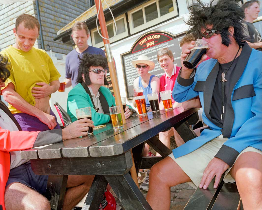 A group of friends in fancy dress drink outside The Sloop Inn pu