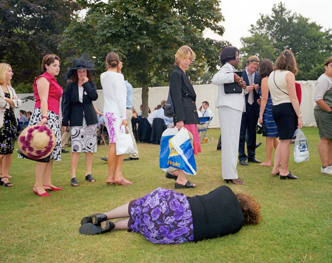A woman lies on the grass next to a queue for the toilet at the