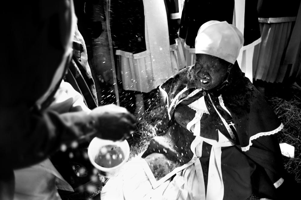همسر کشیش مشغول غسل تعمید یکی از مومنین با ترکیبِ آب رودخانه، خاکستر و چوب کبریت های سوخته است