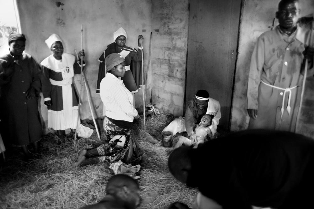 مادر ناظر خروج ارواح خبیثه از بدن دختر کوچکش توسط کشیش است.  بدن لخت کودک با خاکستر پوشانده شده است