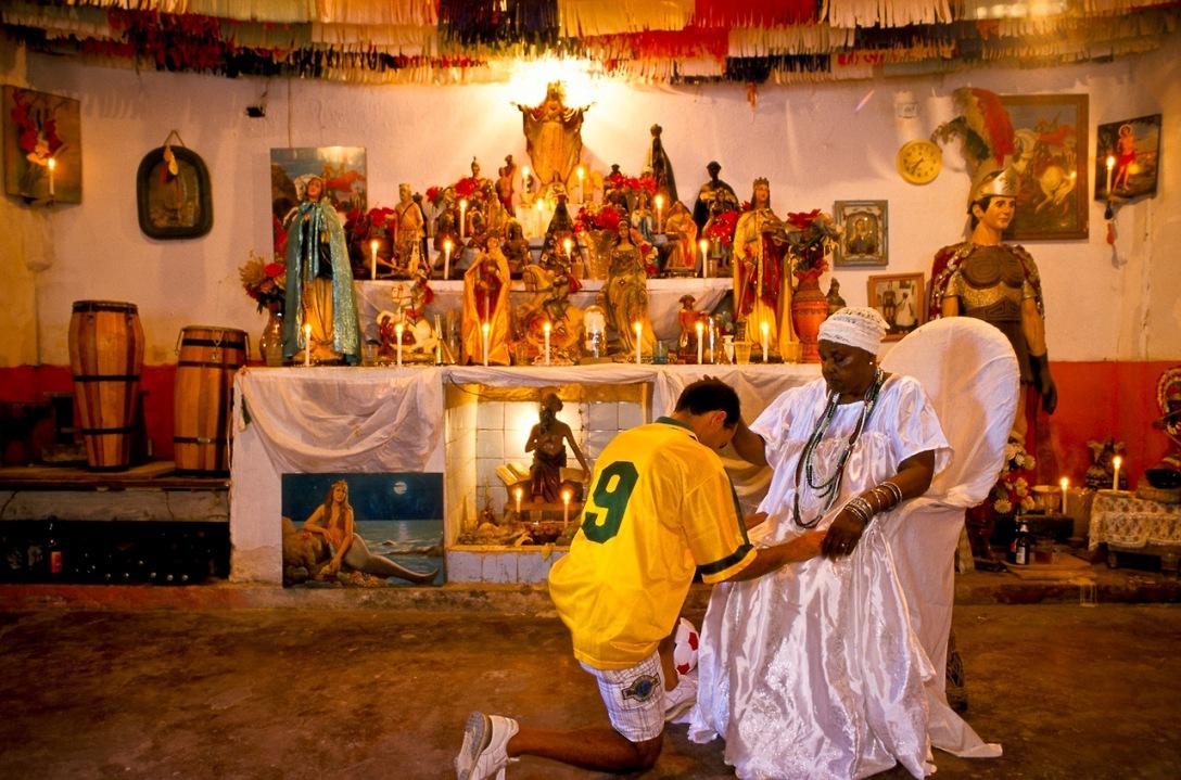 یک کشیش مذهب       یک کشیش مذهب حیوان پرستی Candomble افریقایی در حال تبرک و دعاخوانی برای یک برزیلی است که آمده است از دعای این کشیش برای پیروزی برزیل در جام جهانی کمک بگیرد.