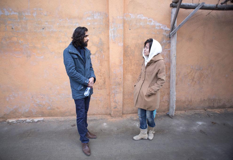 دو دوست مشغول گفتگو در کنار یک قهوه خانه