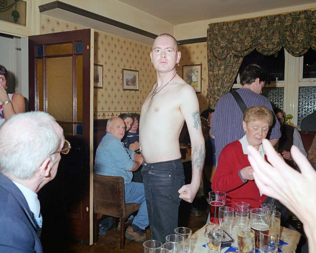 A bare chested skinhead postures for the camera in a pub in Bacu