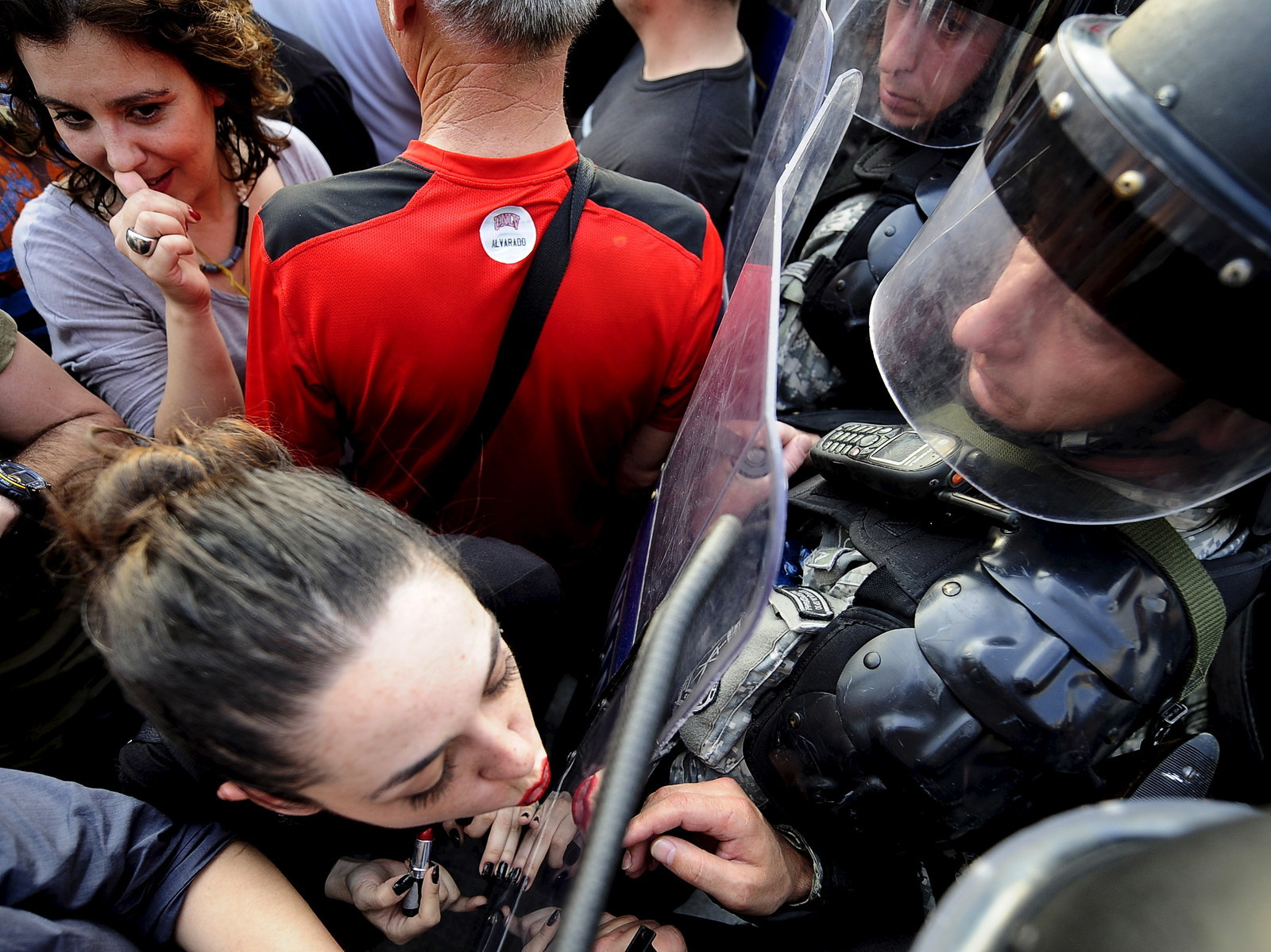 A girl puts on lipstick and kisses the shield of the police in front of the Macedonian government building in Skopje, Macedonia