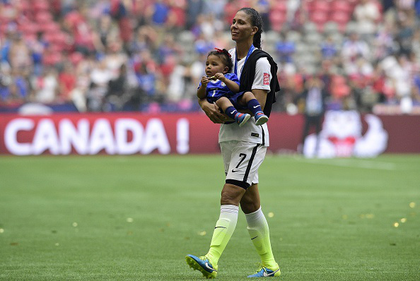 USA midfielder Shannon Box walks on the field with daughter Zoe after winning the final football match between USA and Japan during their 2015 FIFA Women's World Cup at the BC Place Stadium in Vancouver on July 5, 2015.  AFP PHOTO / FRANCK FIFE        (Photo credit should read FRANCK FIFE/AFP/Getty Images)