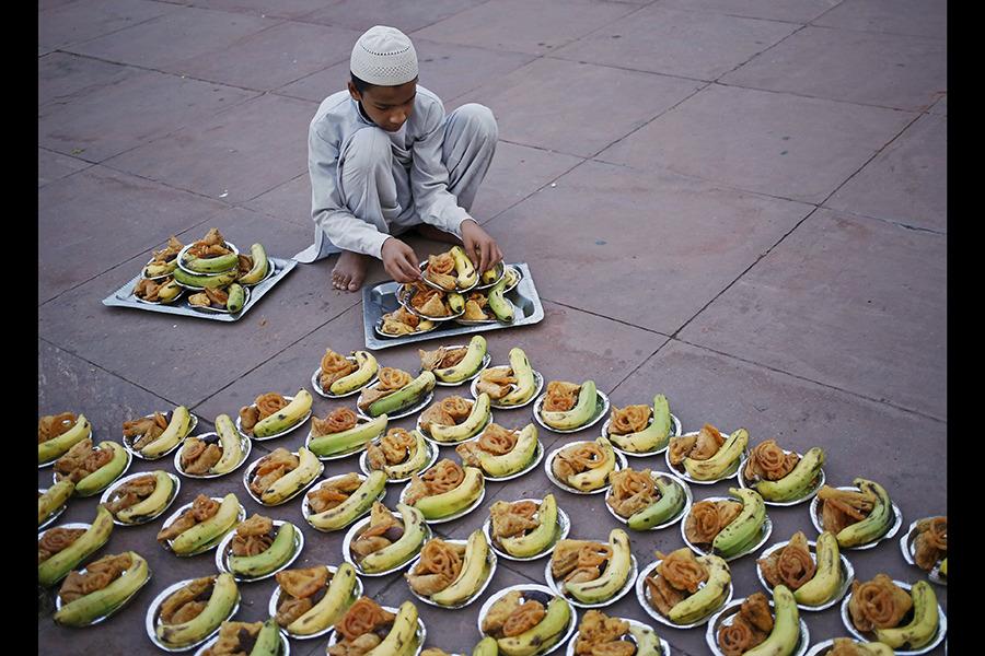 پسر مسلمان مشغول آماده سازی بشقاب افطار در یکی از مساجد دهلی در هند است