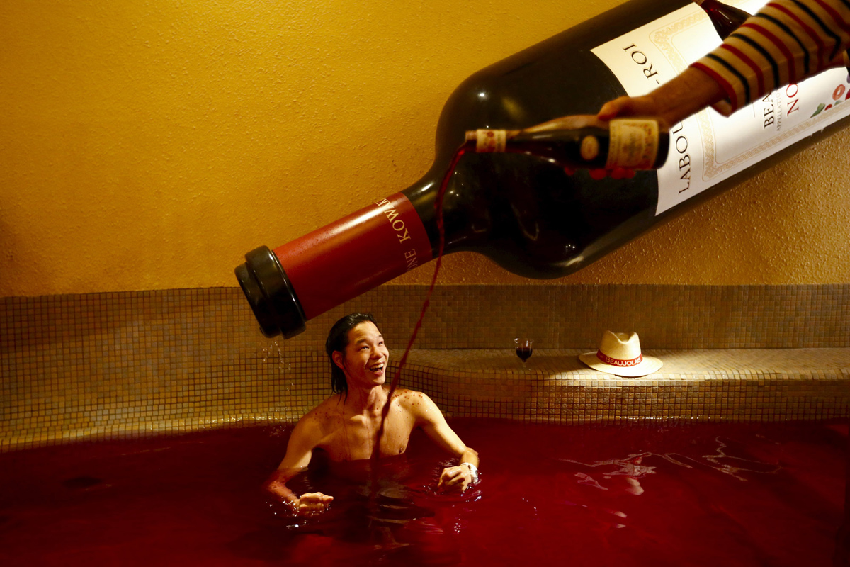 A man pours wine into a hot bath with coloured water representing wine at the Hakone Kowaki-en Yunessun spa resort during an event marking Beaujolais Nouveau Day in Hakone west of Tokyo, November 19, 2015.  REUTERS/Thomas Peter      TPX IMAGES OF THE DAY      - RTS7V05