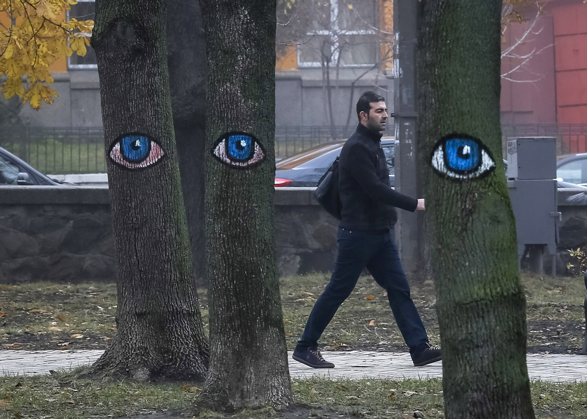A man walks past trees painted with eyes in a park in central Kiev, Ukraine, November 17, 2015.  REUTERS/Gleb Garanich - RTS7IHD