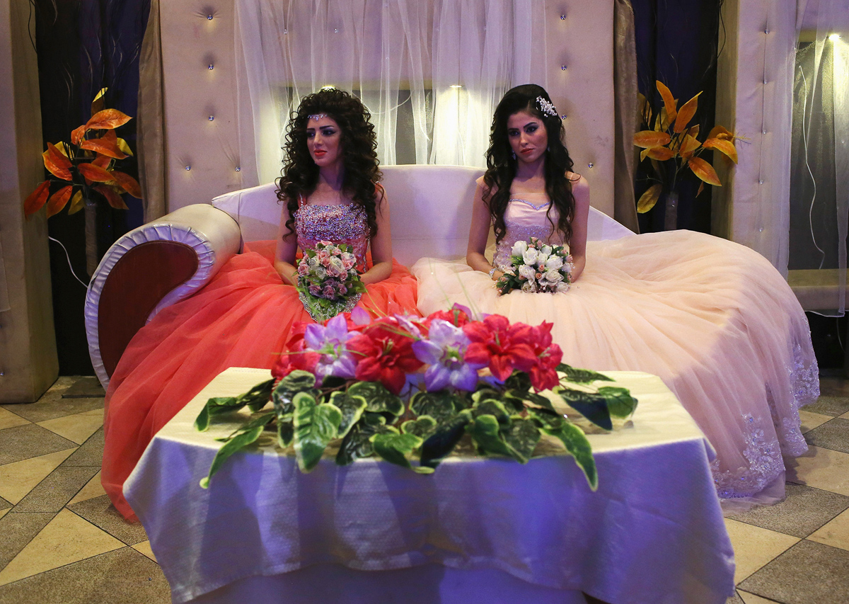 QAMISHLI, SYRIA - NOVEMBER 11:  Kurdish brides Halbast Khalili, 21, (L), and Mezgin Murat, 21, (C), sit on the chez lounge of honor during a wedding reception without their grooms on November 11, 2015 in Qamishli, in the autonomous region of Rojava, Syria. They married their husbands in absentia two months after the brothers successfully immigrated to Germany in the arduous journey as refugees. The women plan to join their husbands in Europe once their immigration documents have been processed.  (Photo by John Moore/Getty Images)