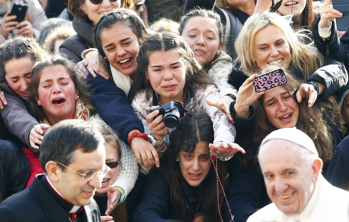 Faithful greet Pope Francis as he arrives to lead the weekly audience in Saint Peter's Square at the Vatican