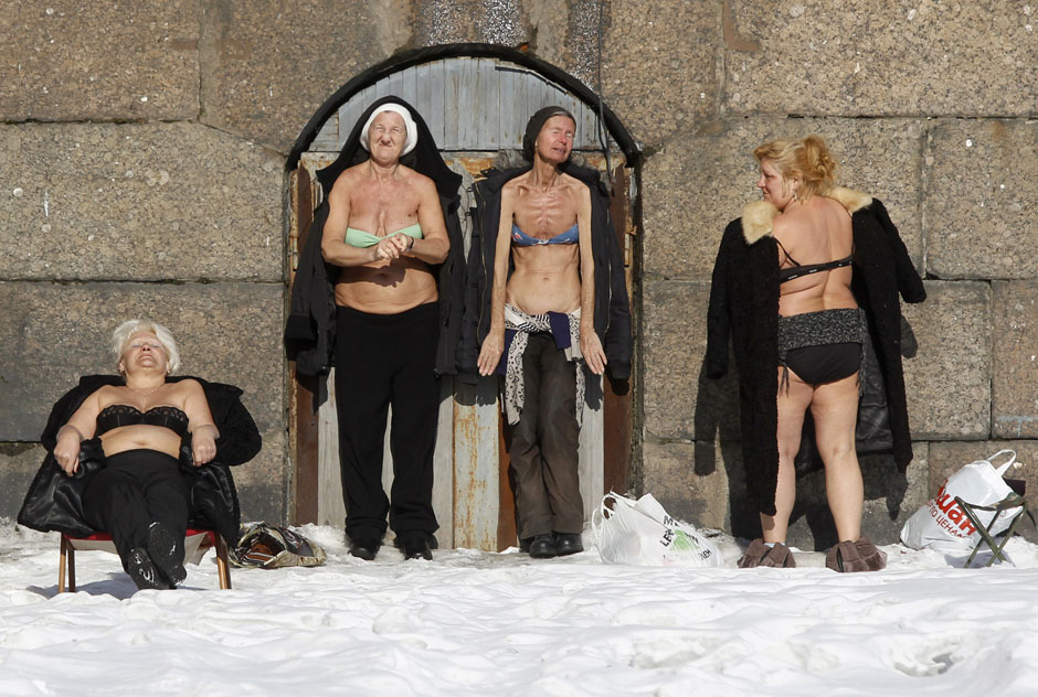 People sunbathe by the wall of the Peter and Paul Fortress in St. Petersburg March 10, 2013. REUTERS/Alexander Demianchuk (RUSSIA - Tags: SOCIETY RELIGION TPX IMAGES OF THE DAY) - RTR3ET00
