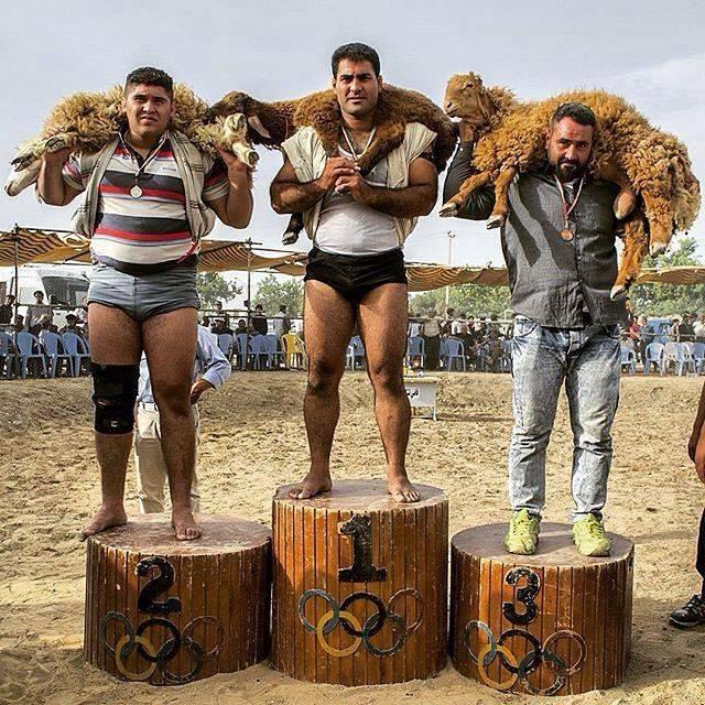 برندگان مسابقات قهرمانی کشتی چوخه به همراه جوایزشان روی سکو ایستادهاند. شیروان، خراسان_شمالی، عکاس امین آوازاده