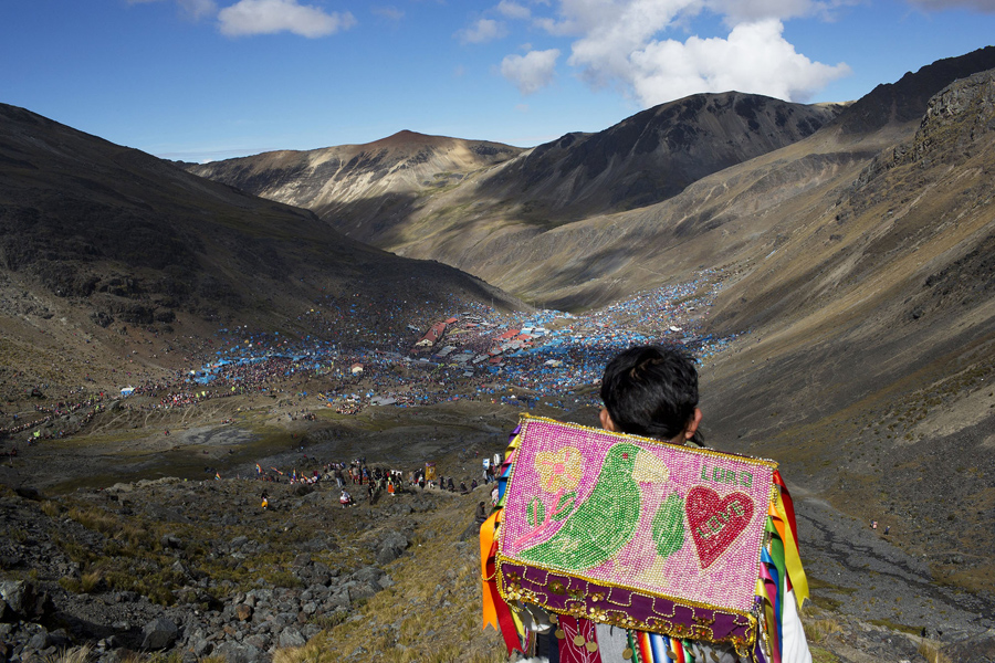 In this May 24, 2016 photo, a young boy descends the Qullqip'unqu mountain looking out at the tens of thousands of pilgrims gathered to celebrate the three-day festival Qoyllur Rit'i, translated from the Quechua language as Snow Star, in the Andean Sinakara Valley, in Peru's Cusco region. The celebration that mixes Catholic and indigenous beliefs honors Jesus as well as the area's glacier, which is considered sacred among some indigenous people. While the native celebration is far older, the Christian part of the ritual stretches back to the 1700s, when Jesus is said to have appeared to a young shepherd in the form of another boy. (AP Photo/Rodrigo Abd)