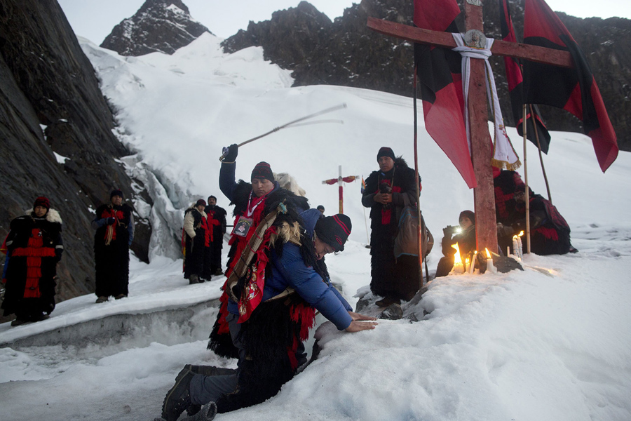 "In this May 24, 2016 photo, an ""ukuku"" pledge places his hands on the ice of the Qullqip'unqu mountain glacier, kneeling before a cross as he is whipped three times by an ukukus leader, in an induction ceremony, as part of the syncretic festival Qoyllur Ritíi, translated from the Quechua language as Snow Star, in the Sinakara Valley, in Peru's Cusco region. New recruits promise to make the pilgrimage three years in a row. (AP Photo/Rodrigo Abd)"