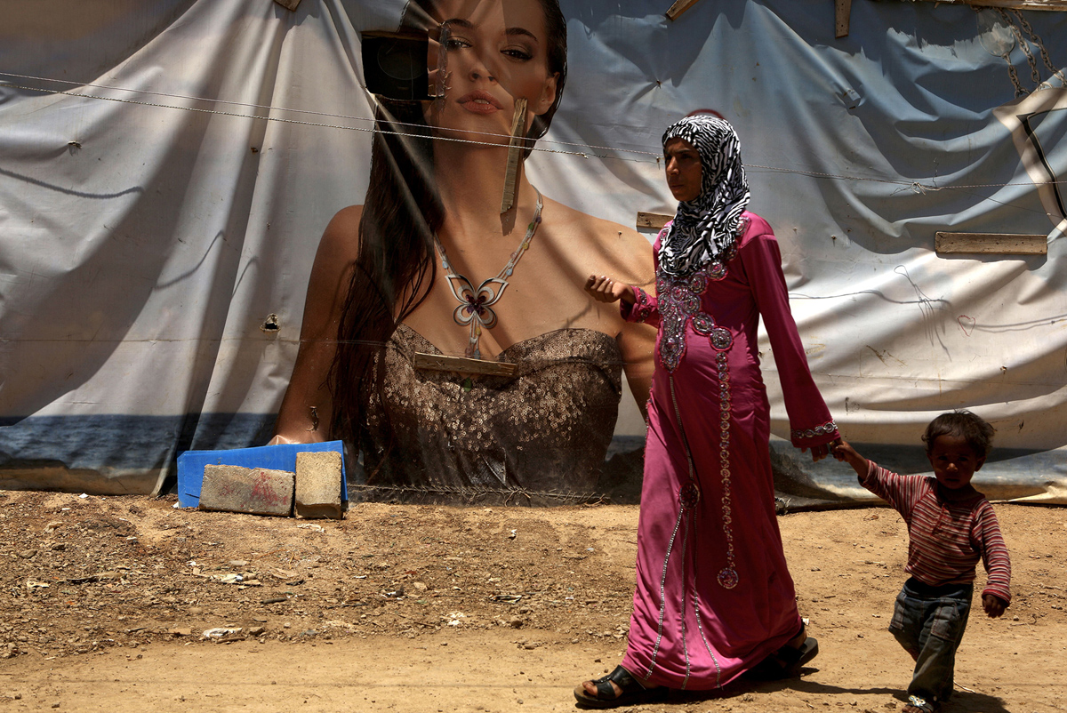 A Syrian refugee from Aleppo holding her son's hand walks past an advertising banner used as a makeshift tent in a Syrian camp