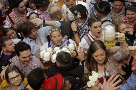 A waitress is surrounded by visitors during the opening ceremony of the 183rd Oktoberfest beer festival in Munich, southern Germany, Saturday, Sept. 17, 2016. The world's largest beer festival will be held from Sept. 17 to Oct. 3, 2016. (AP Photo/Matthias Schrader)