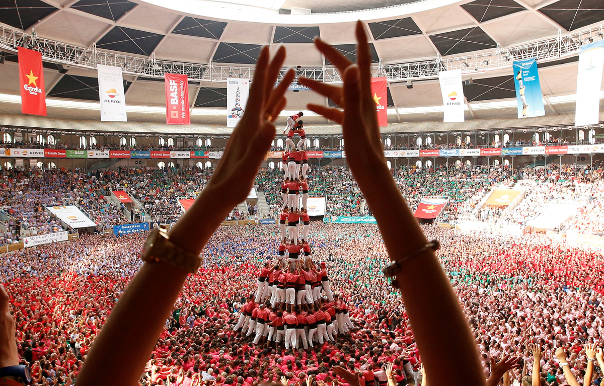 "Colla Vella Xiquets de Valls form a human tower called ""castell"", while a supporter applauds, during a biannual competition in Tarragona city, Spain, October 2, 2016. REUTERS/Albert Gea - RTSQEXF"