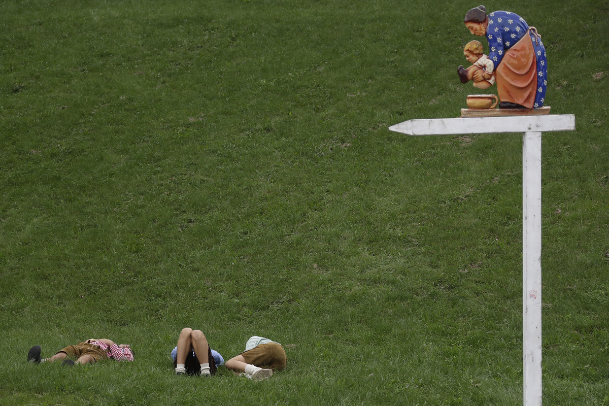 Young visitors rest on a meadow at the 183rd Oktoberfest beer festival in Munich, southern Germany, Tuesday, Sept. 20, 2016. The world's largest beer festival will be held from Sept. 17 to Oct. 3, 2016. (AP Photo/Matthias Schrader)