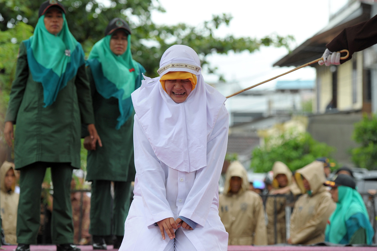 CORRECTION - A Muslim woman gets caned 23 strokes after being caught in close proximity with her boyfriend in Banda Aceh on October 17, 2016. Out of seven couples caught spending time together outside marriage, 13 were caned while one woman was spared after it was discovered that she was pregnant. Indonesia's Aceh province has gained international infamy for its strict Islamic laws. / AFP / CHAIDEER MAHYUDDIN / The erroneous mention[s] appearing in the metadata of this photo by CHAIDEER MAHYUDDIN has been modified in AFP systems in the following manner: [WOMAN] instead of [GIRL]. Please immediately remove the erroneous mention[s] from all your online services and delete it (them) from your servers. If you have been authorized by AFP to distribute it (them) to third parties, please ensure that the same actions are carried out by them. Failure to promptly comply with these instructions will entail liability on your part for any continued or post notification usage. Therefore we thank you very much for all your attention and prompt action. We are sorry for the inconvenience this notification may cause and remain at your disposal for any further information you may require. (Photo credit should read CHAIDEER MAHYUDDIN/AFP/Getty Images)